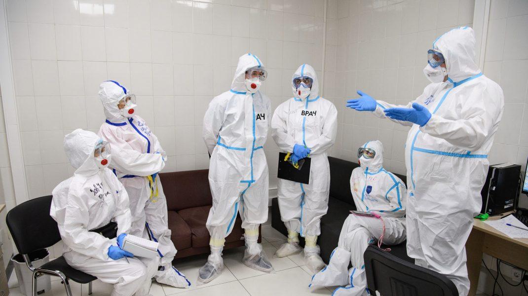 Medici îmbrăcați în echipamente COVID-19.