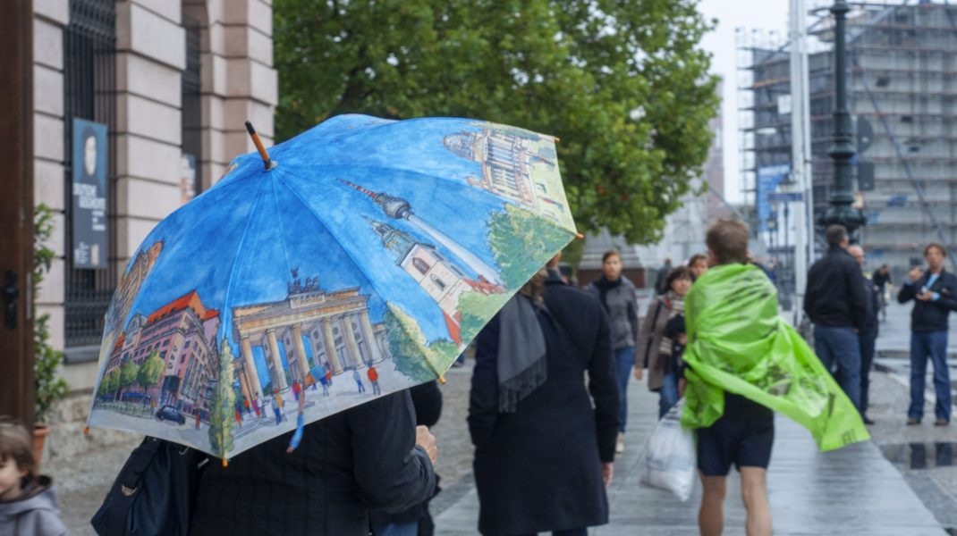 Oamenii care merg cu umbrela prin ploaie.