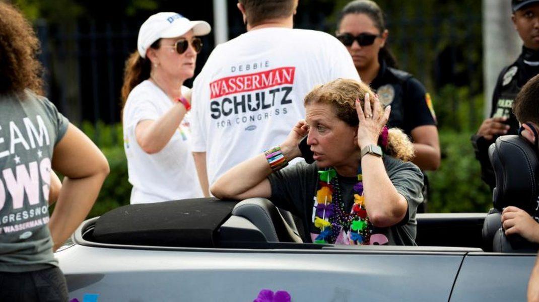 Femeie care sună după ajutor după un accident petrecut în timpul unei parade LGBT.