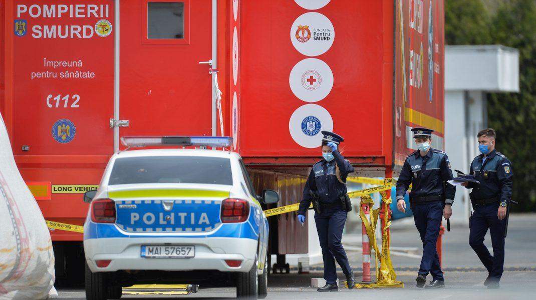 Polițiști lângă o mașină de poliție și o autospecială SMURD.