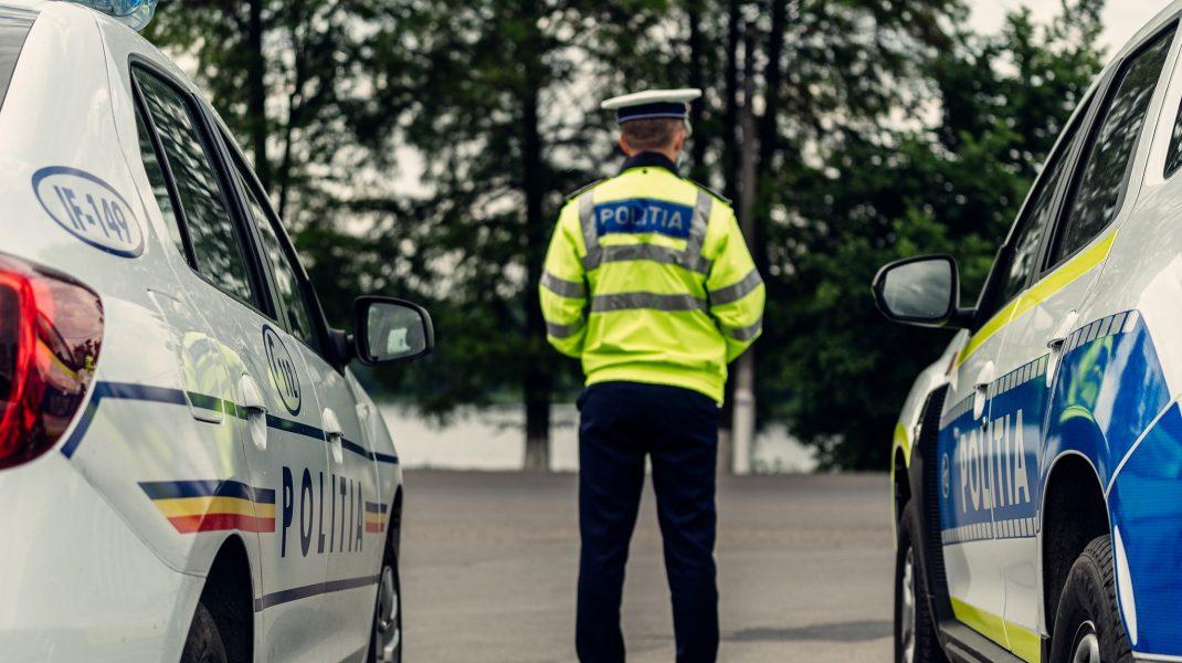 un politist intre doua masini de politie.