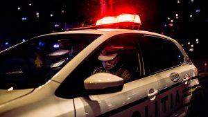 politisti intr-o masina de politie, noaptea.