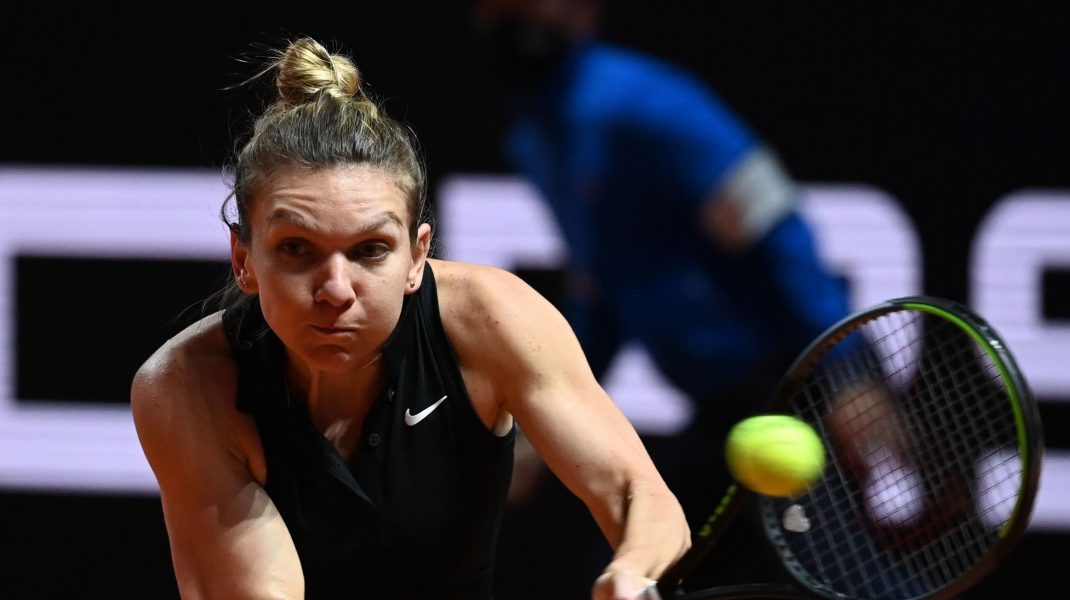 Simona Halep lovește cu racheta într-o minge de tenis.
