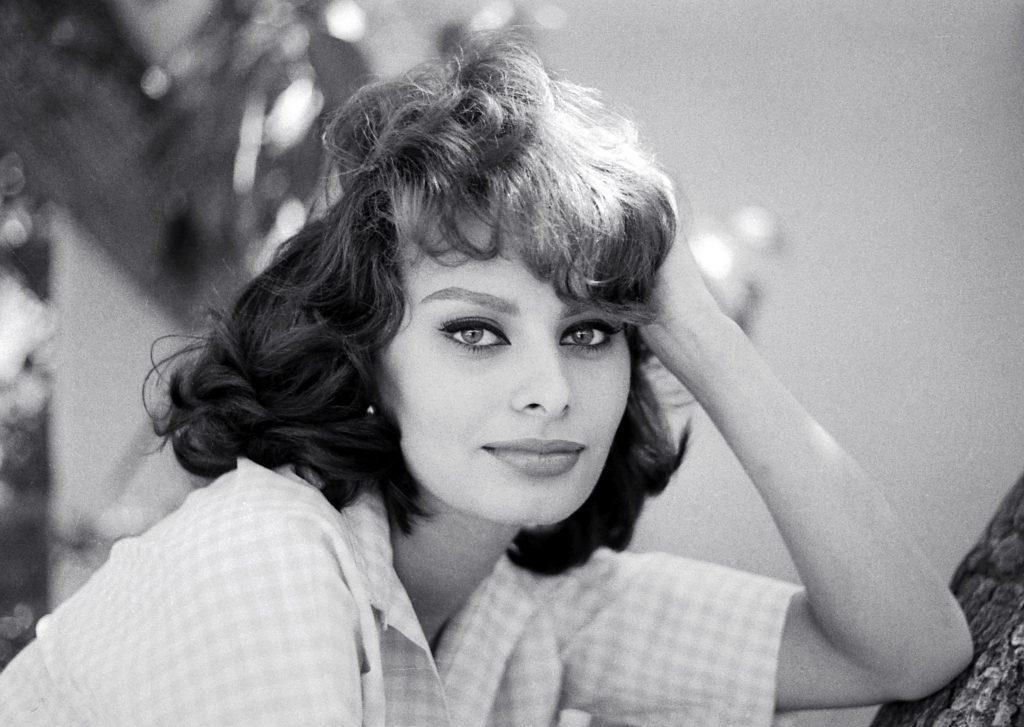 Actrița Sophia Loren se uită spre aparatul de fotografiat, iar fotografia este alb-negru.