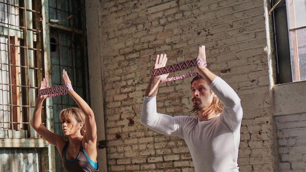 O femeie și un bărbat care fac sport într-o sală de fitness.