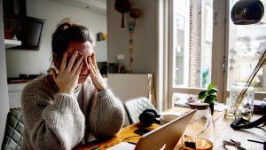 Tânără care stă la birou, își pune mâinile la ochi și pare obosită.