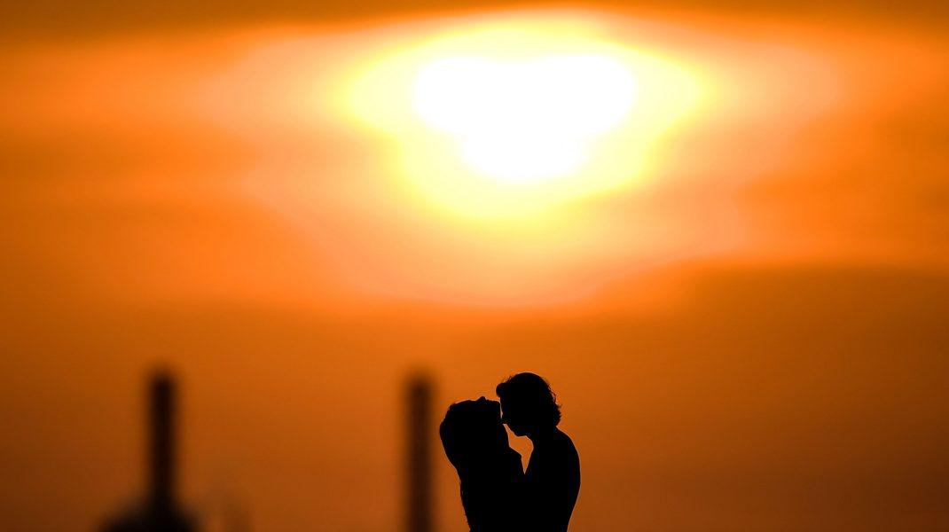 doi tineri in fata unui cer portocaliu