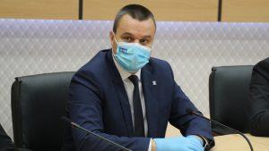 Eugen Pîrvulescu cu masca si manusi la un birou.