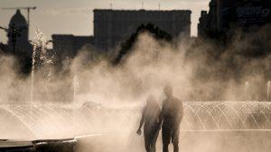 Un cuplu care se plimbă pe lângă o fântână în București, pe vreme de caniculă.