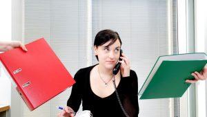 Femeie care se află la birou și vorbește la telefon.