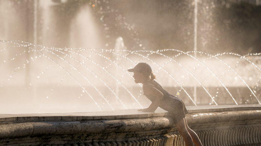 Fetiță care stă lângă fântână în București.