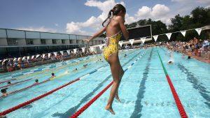 o fetita sare in piscina la un concurs de natatie in aer liber.