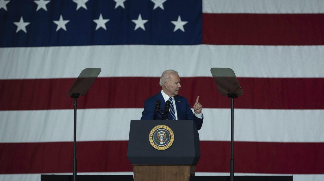 Joe Biden cu drapelul SUA în spate.
