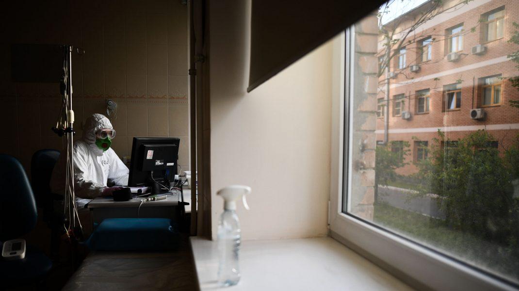 Medic care lucrează la laptop într-un salon de spital.