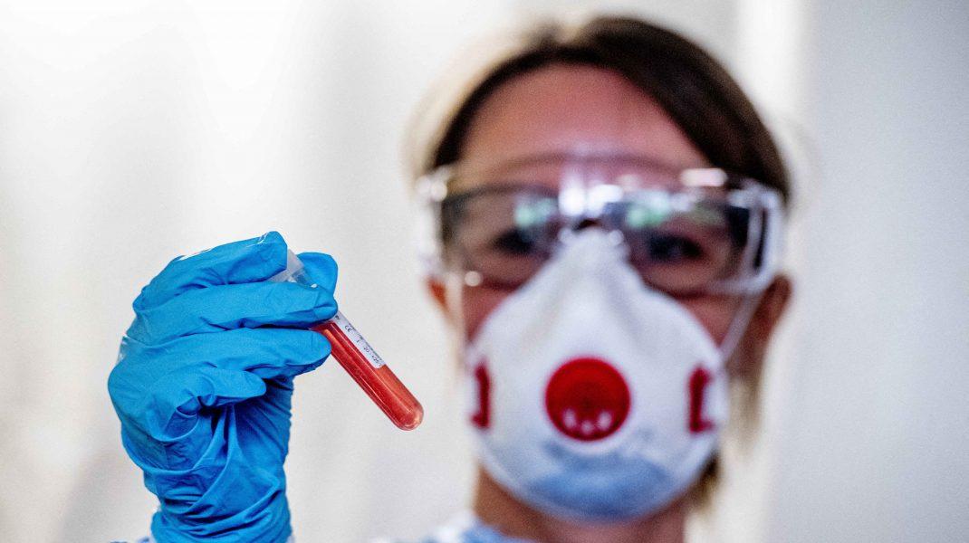 Medic care ține în mână un test de sânge COVID.