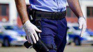 Agent de poliție din România care ține mâna lângă pistol.