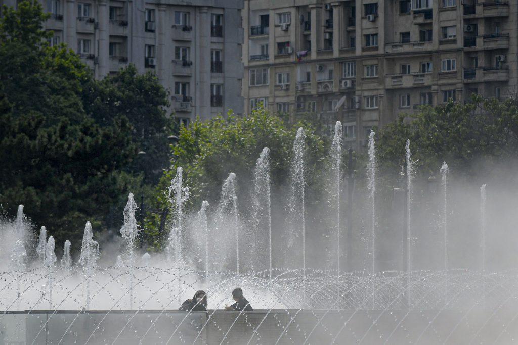 Doua tinere discuta langa fantanile din Piata Unirii, intr-o zi caniculara, in Bucuresti, sambata, 4 iulie 2020.