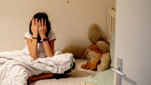 Copil care stă în dormitor, în pat, cu mâinile la ochi.
