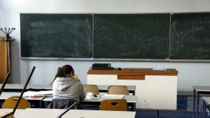 Elev care stă în bancă la școală.