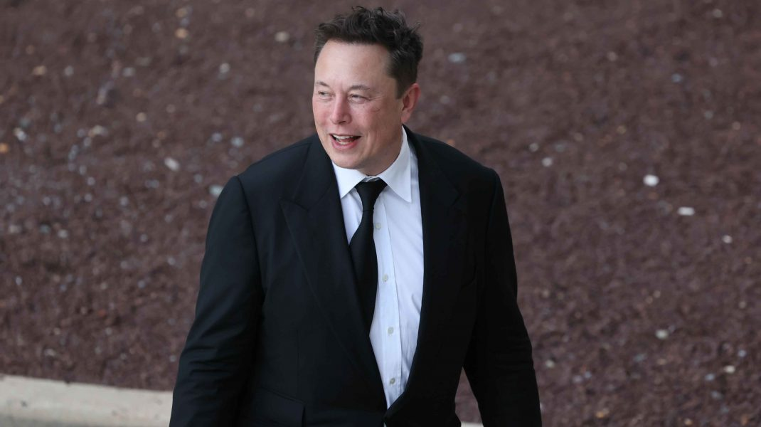 Elon Musk fotografiat lângă o mașină.