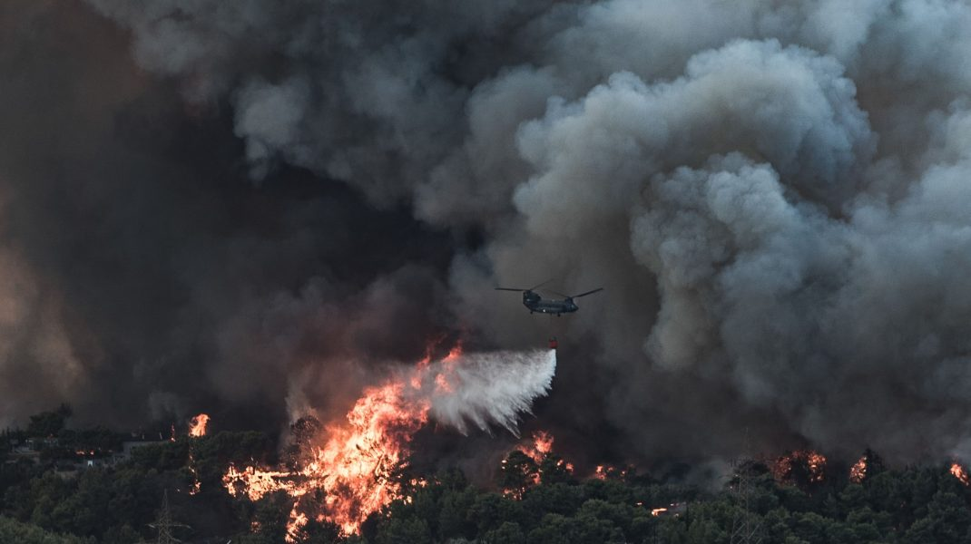 Un avion aruncă apă asupra unui incendiu de vegetație izbucnit într-o zonă forestieră din Tatoi, Grecia. Foto: Hepta