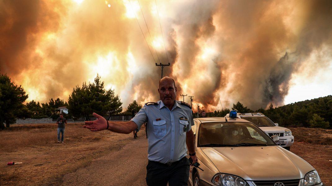 05 august 2021, Grecia, Atena: Un ofițer de poliție lucrează pentru a evacua zona din apropierea unui incendiu de vegetație care arde zona Drossopigi, Varybobi, o suburbie din nord-estul Atenei.