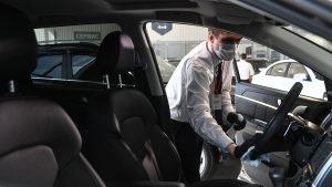 Angajat al unui showroom auto care face curat într-o mașină.