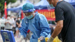Medic chinez care se pregătește să teste o persoană pentru COVID.