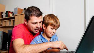 un barbat si un copil se uita la un laptop