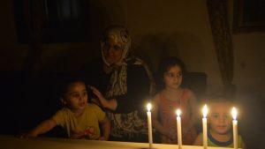 o femeie si copii pe intuneric, in liban, folosesc lumanari.